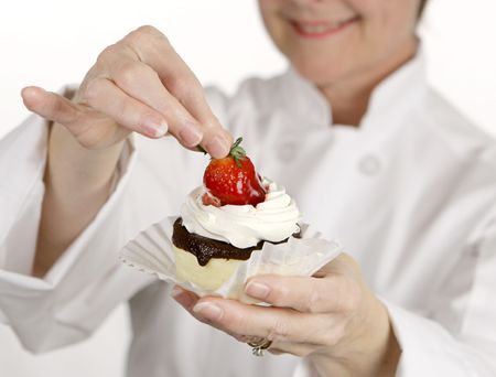 woman baking: Closeup of a strawberry cheesecake tart held by the pastry chef who created it.