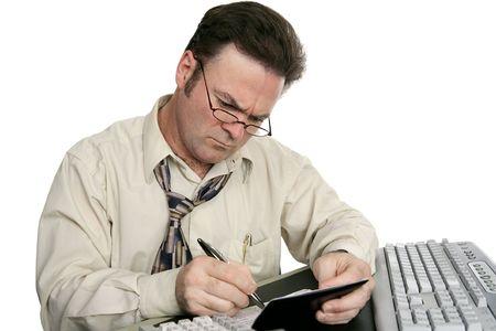 chequera: Un hombre se concentra en equilibrar su chequera. Aislado en blanco.  Foto de archivo