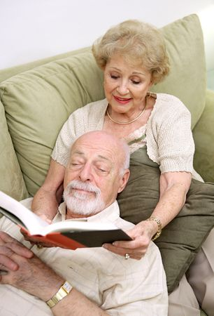 A senior couple reading together.  The wife is reading to the husband.   photo