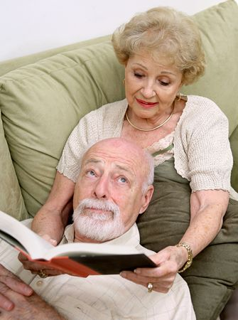 A senior woman reading to her husband who is rolling his eyes in boredom. photo