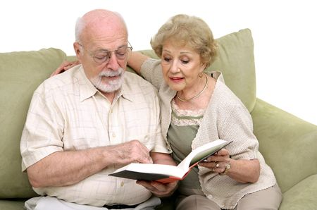 An attractive senior couple spending time reading together. Isolated on white. photo
