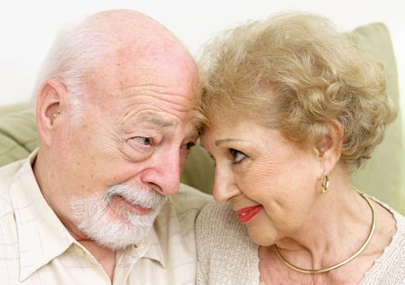 eachother: A senior couple looking at eachother lovingly nose to nose.   Stock Photo