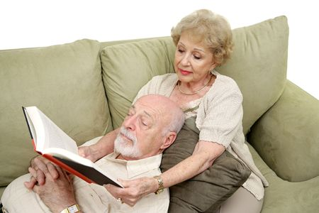 taking a wife: A senior man taking an afternoon nap while his wife reads to him.  White Background. Stock Photo
