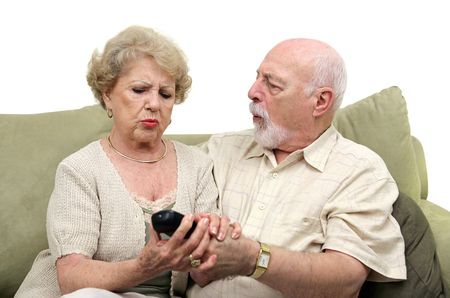 A senior couple fighting over the television remote control.  White background. photo