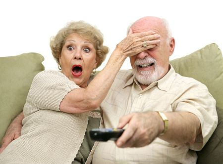 A senior couple shocked by what they see on television.  Shes covering his eyes and hes changing the channel.  White background.