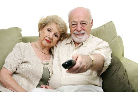 Seniors watching television together and switching channels.  White background. photo