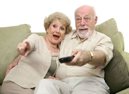really: A senior couple really enjoying a television program.  White background.