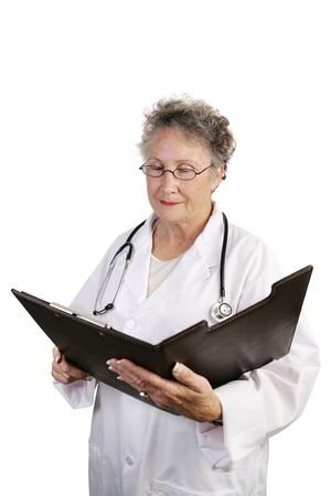 A mature female doctor reviewing a medical chart.  Isolated on white. photo