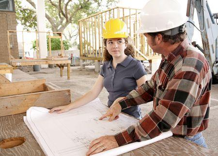 apprenti: Un apprenti de construction �coutant en tant que son agent de ma�trise va au-dessus des mod�les.