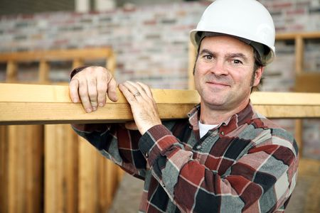 builders: A friendly appealing construction worker in classic pose, carrying planks on the jobsite.  Model is actual construction worker. Authentic and accurate content depiction.
