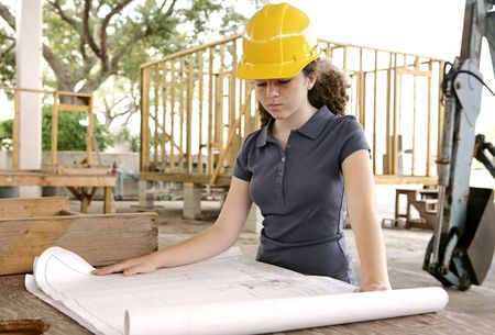 the job site: Una femmina studente di ingegneria e il lavoro di revisione del sito blueprint.  Archivio Fotografico