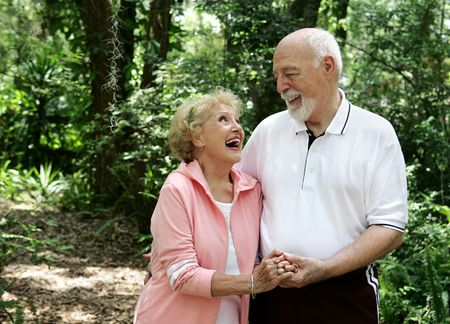 A happy, active senior couple laughing together on a walk through the park.  Shes wearing a hearing aid.  Plenty of copyspace.