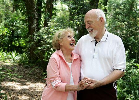actief luisteren: Een gelukkig, actieve senior paar lachen samen op een wandeling door het park. Ze is het dragen van een gehoorapparaat. Plenty of copyspace. Stockfoto