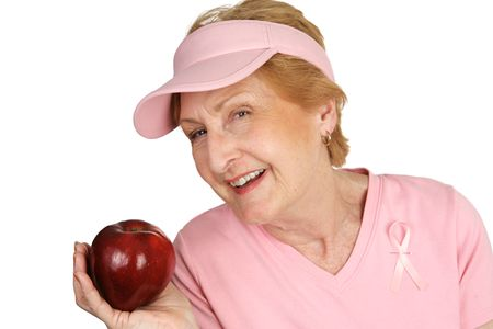 ...keeps the doctor away.    A senior woman dressed for breast cancer awareness holding a bright red apple.  Isolated on white.   photo