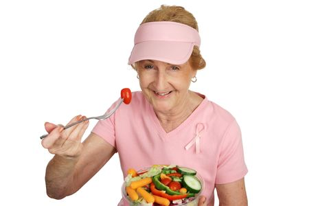 A senior woman in pink with Breast Cancer Awareness ribbon, eating healthy salad.  Isolated on white. photo