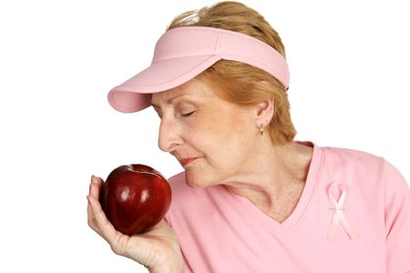 A woman dressed in pink with breast cancer awareness ribbon, smelling delicious red apple.  Emphasizes healthy eating to beat cancer.  Isolated on white. photo