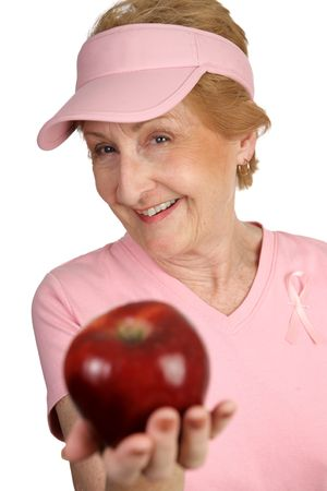 A woman dressed for breast cancer awareness holding out a delicious red apple for you.  Isolated on white. photo