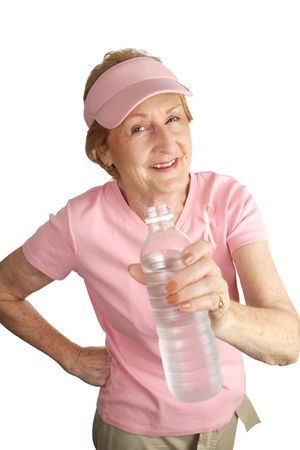 A woman dressed for breast cancer awareness holds out a bottle offering you some cold water.  Isolated on white. photo