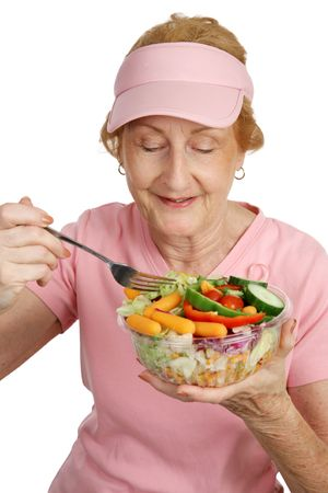 A woman dressed for Breast Cancer Awareness eating a delicious, healthy salad.  White background. photo