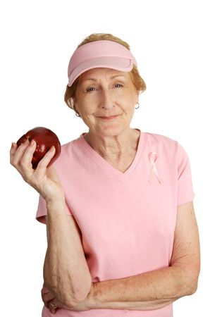 A senior woman dressed in pink for breast cancer awareness holding a red apple for a healthy snack.  Isolated on white.   photo