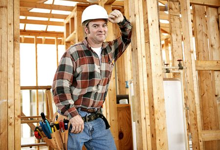 building contractor: A construction worker with his tools on the jobsite.  Authentic construction worker on actual construction site.   Stock Photo