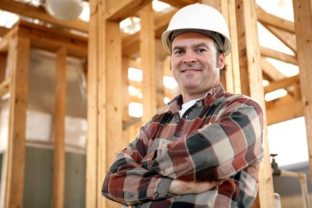 constructeur: Un ouvrier beau et amical de construction sur lemplacement du travail. Ouvrier authentique de construction sur le chantier de construction r�el. Banque d'images