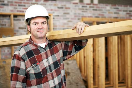 laborer: A construction day laborer carrying wood beams.  Authentic construction worker on an actual construciton site.   Stock Photo