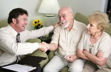 scam: A married senior couple seeing a counselor or salesman.  The men have reached and agreement and the wife looks angry.   Stock Photo