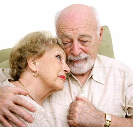 An elderly husband and wife consoling themselves over the loss of a loved one.   photo