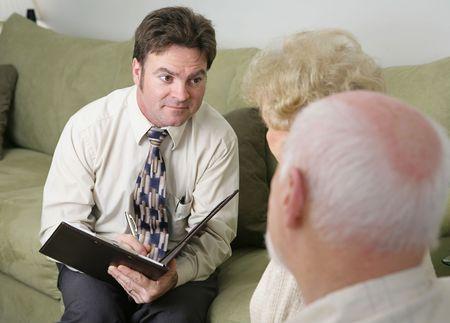Een adviseur met een zorgzame meningsuiting vergadering tegenover een bejaarde echtpaar.