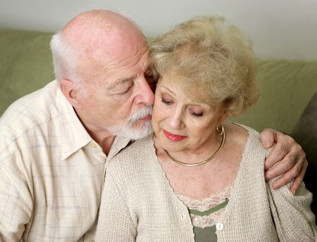 he and she: A senior man and wife deeply in love.  She is upset and he is comforting her.   Stock Photo