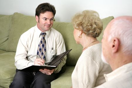 A marriage counselor or salesman listening to an elderly couple.   Could also be a salesman.   photo