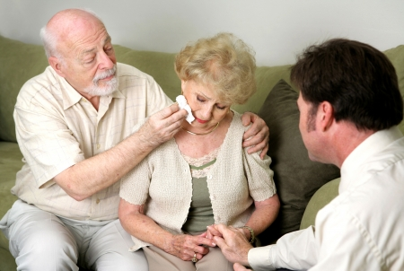 taking a wife: A senior couple with a counselor or funeral director.  She is crying and they are comforting her.   Stock Photo