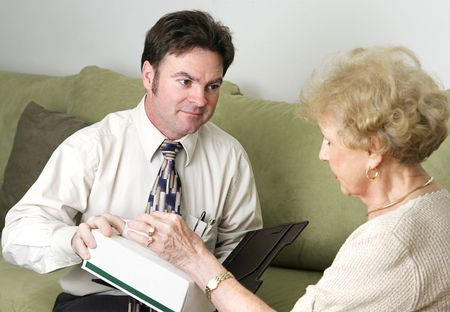 A sympathetic counselor offering an upset client a tissue.