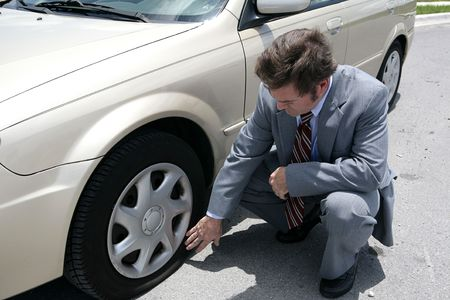 tire: A man dressed for a business meeting discovering a flat tire on his car.   Stock Photo