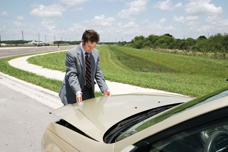 inconvenient: A businessman with car trouble checking under the hood.