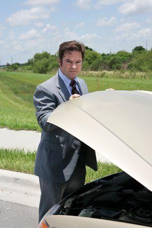 inconvenient: A businessman whose car has broken down, checking under the hood.