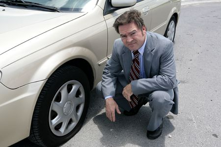 flatten: A businessman on the road with a flat tyre.  He looks upset.