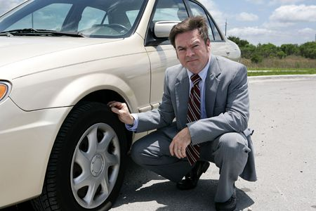 flat tyre: An unhappy looking businessman discovering a screw in his flat tyre.