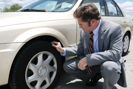 tire tread: A businessman on the road with a flat tyre.  He has just discovered the screw that caused the tyre to go flat.