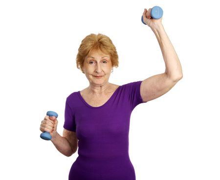 strong: A seventy year old woman smiling and working out with weights.  Isolated on white.   Stock Photo