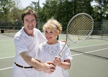 gigolo: A fit senior lady getting a tennis lesson from a handsome young pro.
