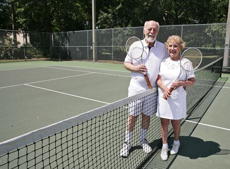 A happy active senior couple on the tennis courts.  Wide view with room for text.