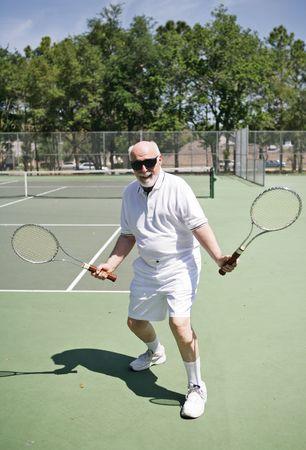 backhand: Un activo hombre de categor�a superior en una pista de tenis, con dos raquetas buscando a alguien para jugar.