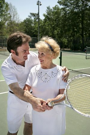gigolo: A pretty senior woman getting a tennis lesson from a handsome young pro.