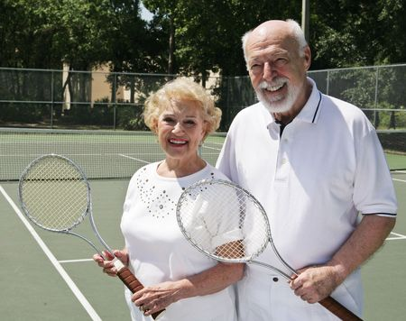 An active, happy senior couple on the tennis courts.   photo