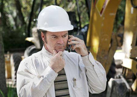 An engineer on a construction site talking on his phone and thinking.   photo