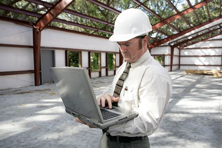 A construction inspector or engineer filling out his report on his laptop.