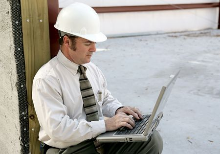An engineer on a construction site using a laptop computer.   photo