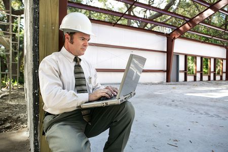 A construction engineer or inspector on the construction site with his laptop. Zdjęcie Seryjne